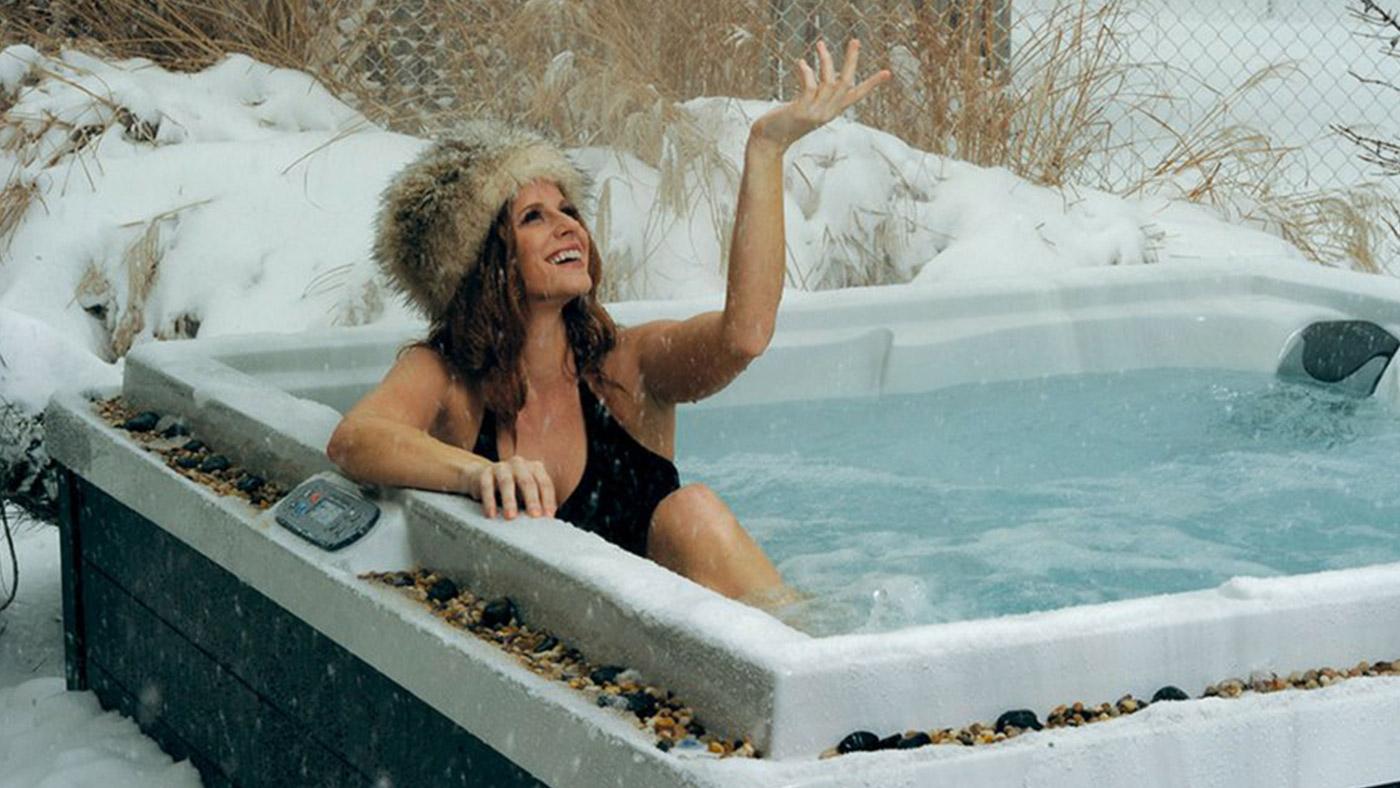 woman in fur hat in hot tub in snow